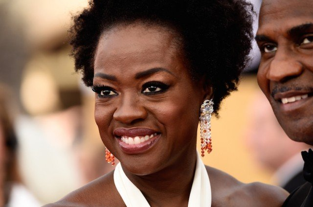 Viola Davis smiling in intricate earrings and a white dress.