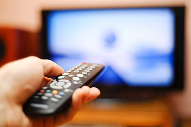 Man holding a remote in his hand pointed at the TV