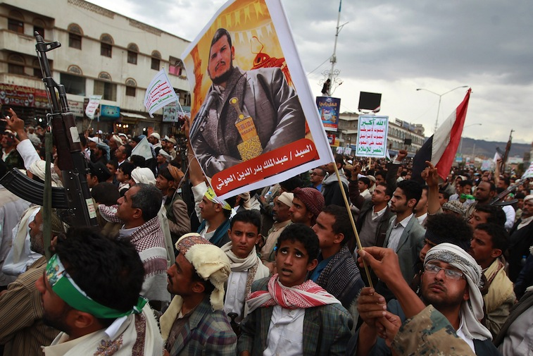 Yemeni supporters of the Shiite Huthi militia hold a portrait the movement's leader, Abdul-Malik al-Huthi