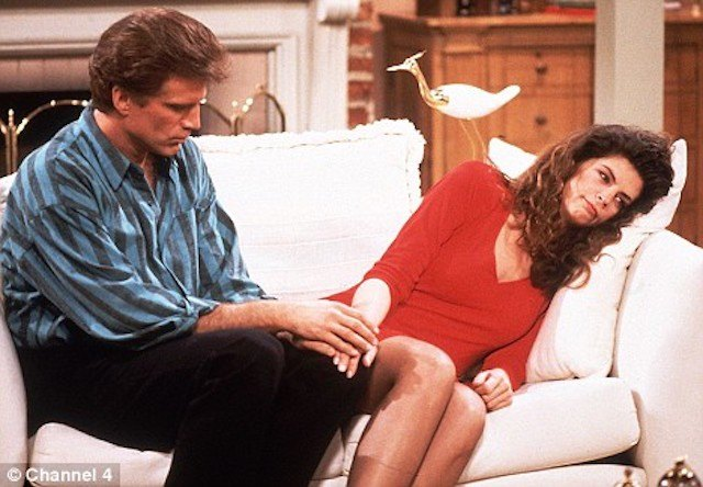 Kirstie Alley lays on a couch while a man holds her hand in Cheers