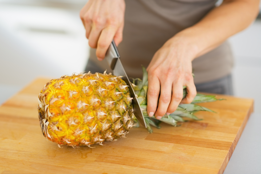 close up of someone cutting a pineapple