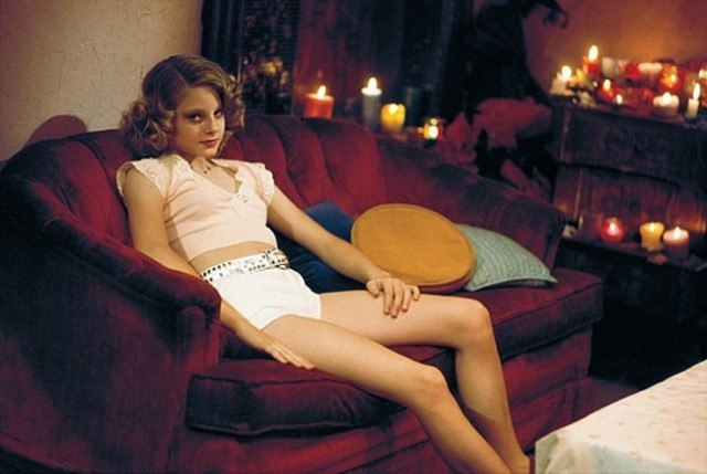 A young Jodi Foster poses on a couch in a scene from Taxi Driver