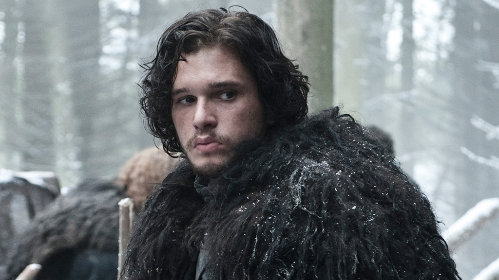 Jon Snow is in a black coat in the snow looking sad.