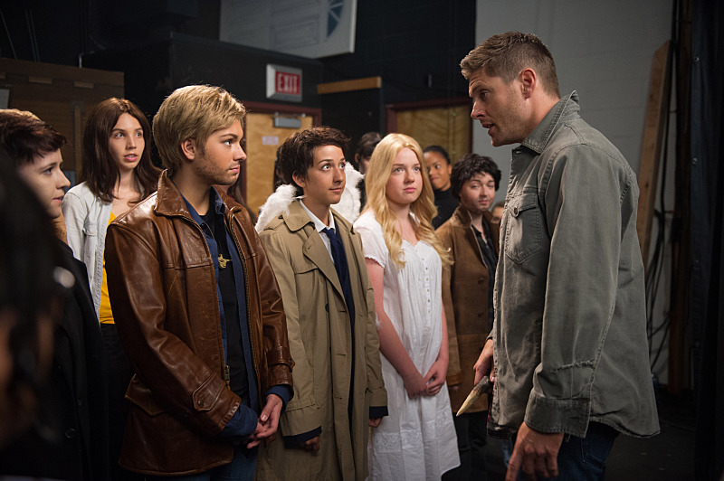 A young girl dressed up like Jensen Ackles, standing on stage with him and a group of other children