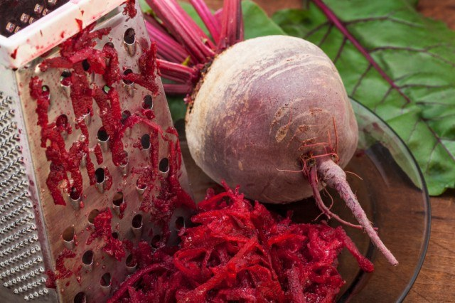 beet being grated into a bowl