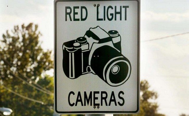 Cars drive past a red light camera sign - Mario Tama/Getty Images