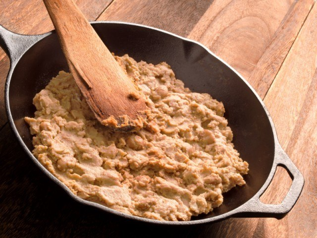A pan of refried beans with a wooden spoon.