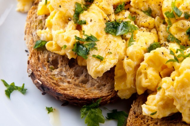 close image of scrambled eggs on toast with herbs