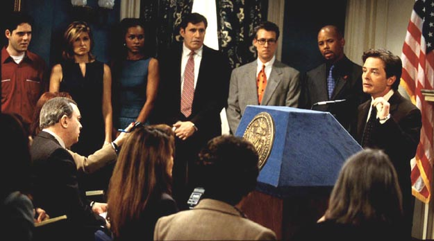 Michael J. Fox stands at a podium in front of a crowded room in Spin City