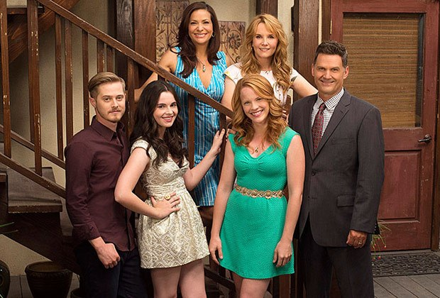 The cast of Freeform's Switched at Birth stand on a staircase in a house, all dressed up