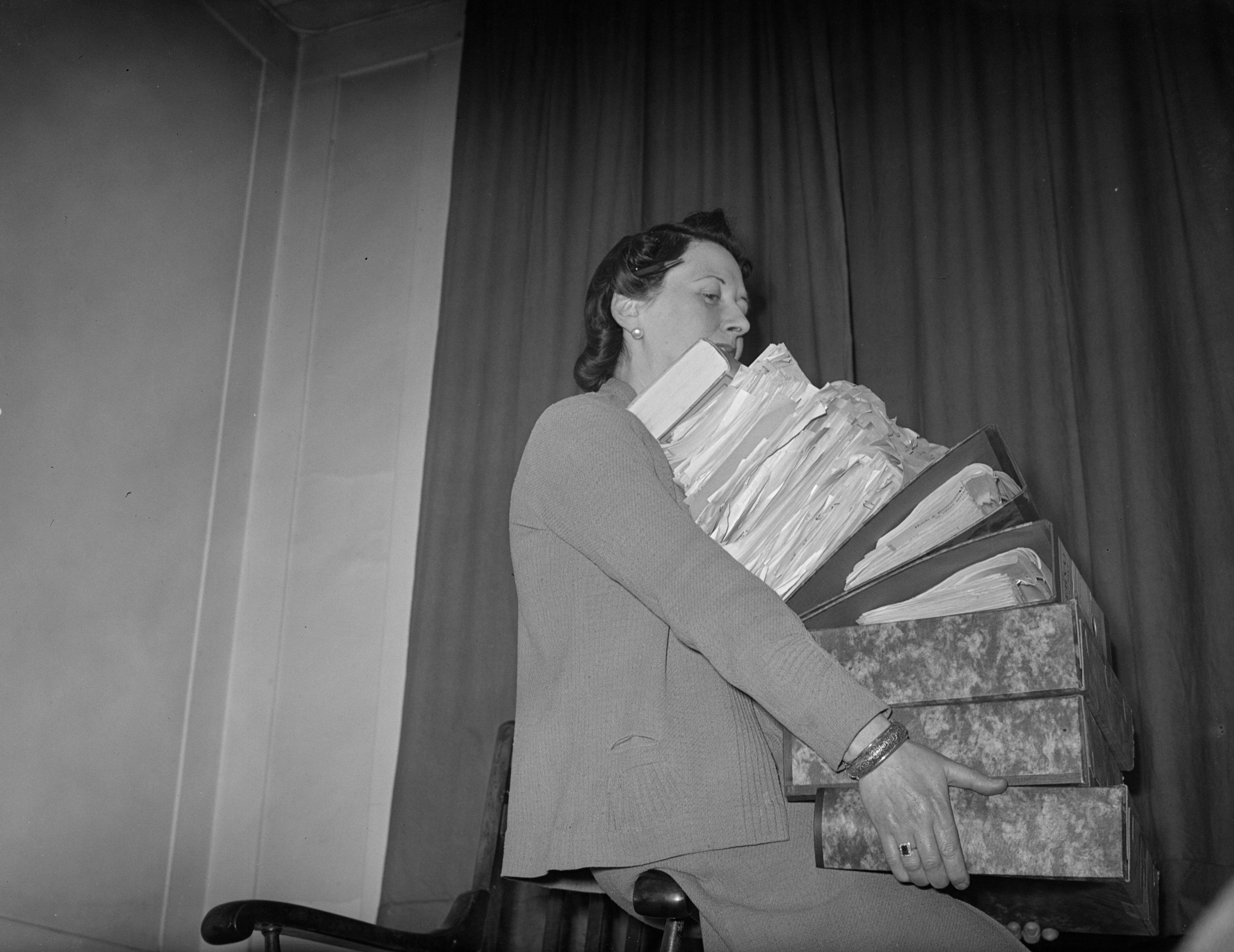 A woman holding a large pile of files and documents in preparation for filling out her tax return
