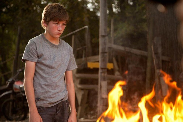 Tye Sheridan stands next to a fire in a scene from Mud