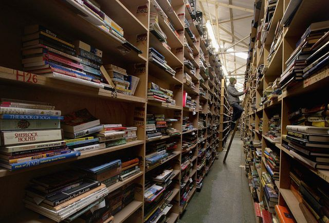 A man looks for a book in a warehouse or library.