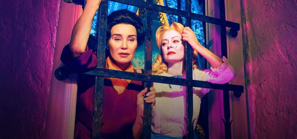 Jessica Lange and Susan Sarandon pose with their arms resting on window bars in FX's Feud