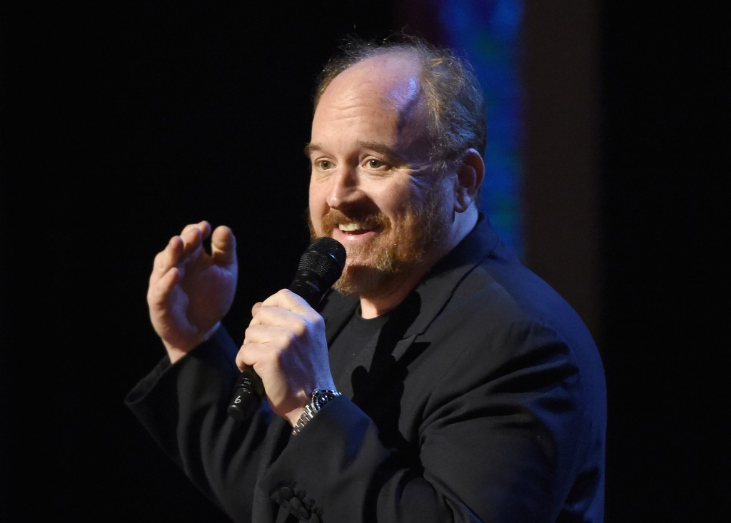 Louis CK speaks into a microphone while performing on stage
