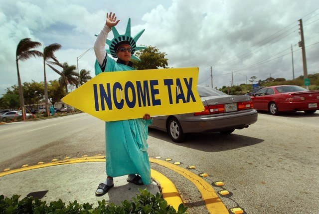 Felipe Castro holds a sign advertising a tax preparation office - Joe Raedle/Getty Images