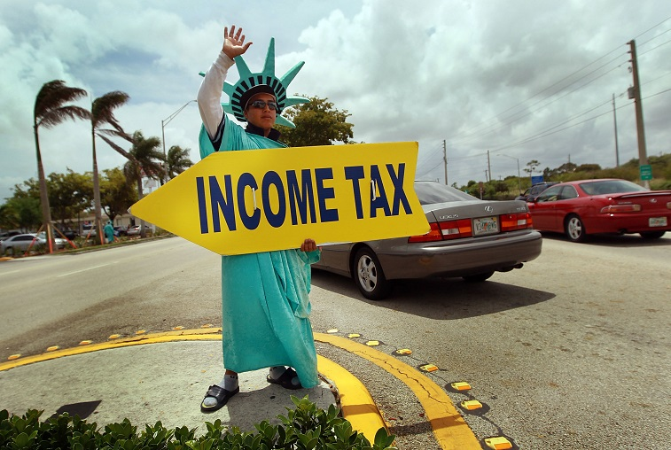 Felipe Castro holds a sign advertising a tax preparation office
