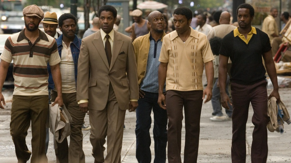 Frank Lucas (Denzel Washington) walks on a sidewalk in New York flanked by his business associates.