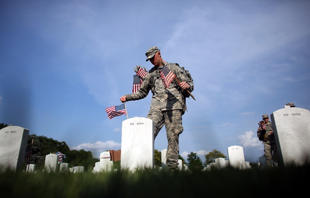 Members of the 3rd U.S. Infantry Regiment place American flags at the graves of U.S. soldiers.