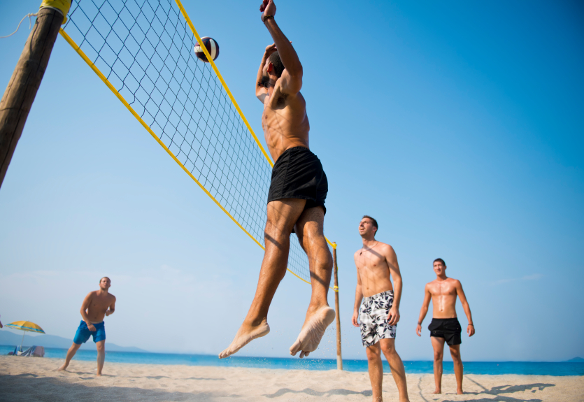 group of friend playing volleyball at the beach