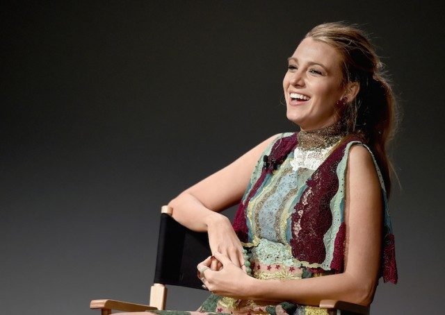 Blake Lively laughing while sitting on a chair on stage.