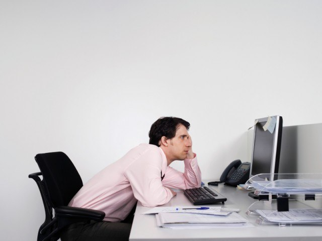 man slumped over his desk at work could be causing back pain