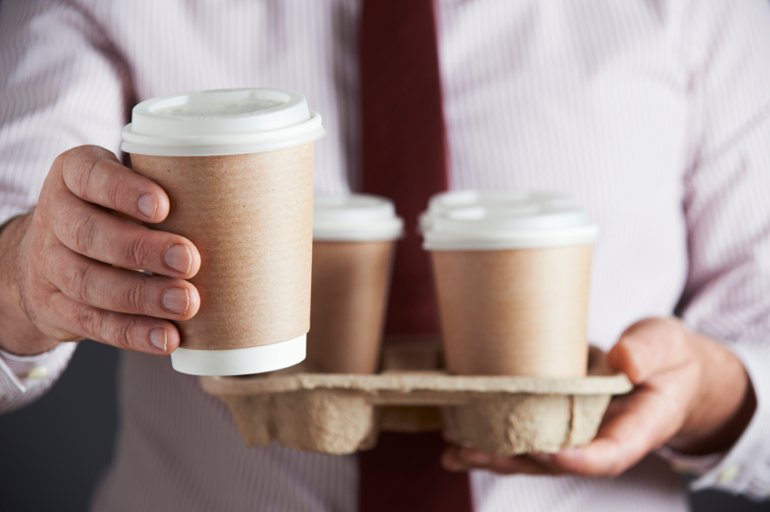 man holding cups of coffee in to-go containers