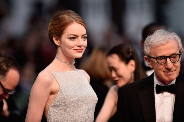 Emma Stone standing with Woody Allen on a red carpet.