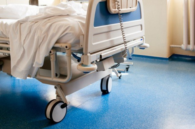 A hospital bed with wheels on a blue floor.