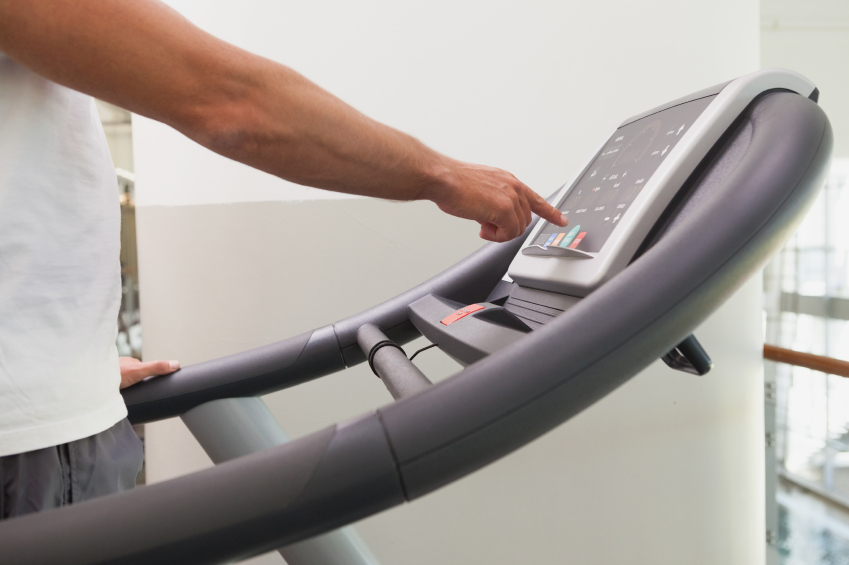 man touching the screen of a treadmill