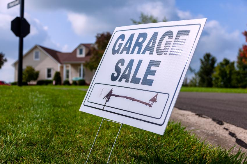 a garage sale sign in a yard