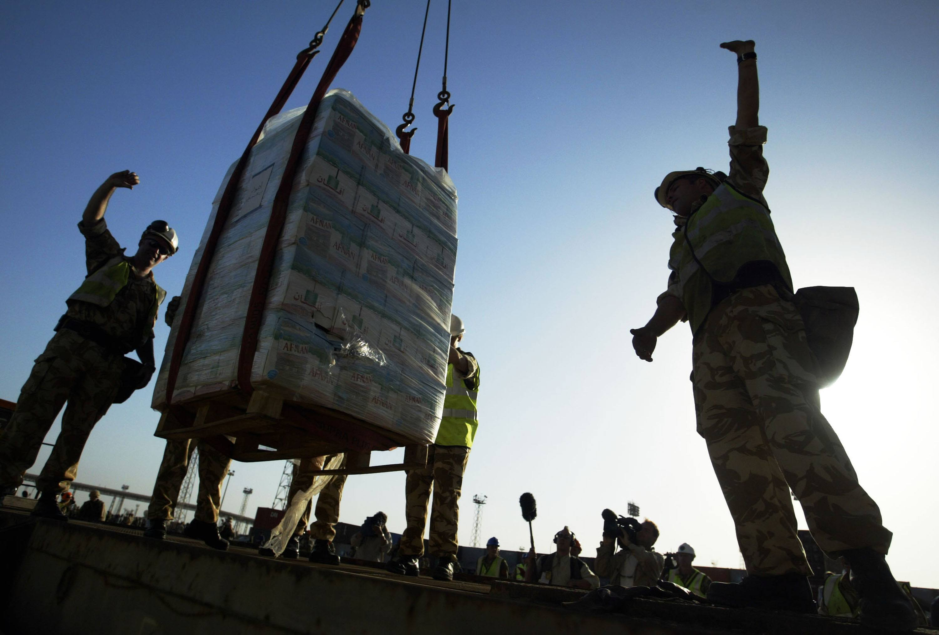 A pallet of fresh bottled water is lowered onto a dock in Iraq