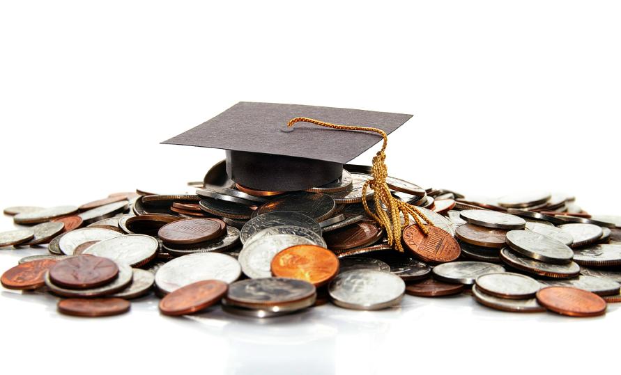 A graduation cap on a pile of change