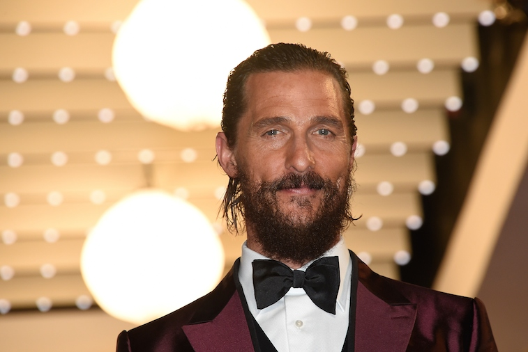 Matthew McConaughey smiling in front of lights wearing a black bowtie