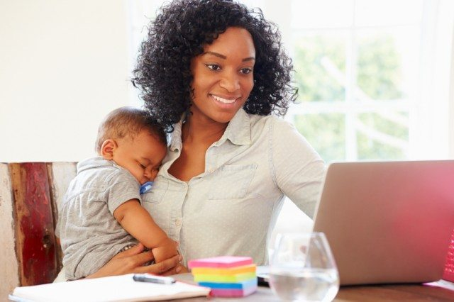 woman working at laptop and holding her baby