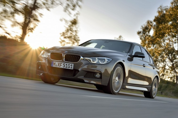 Worm's eye view of a 2015 BMW 3-Series sedan on a country road