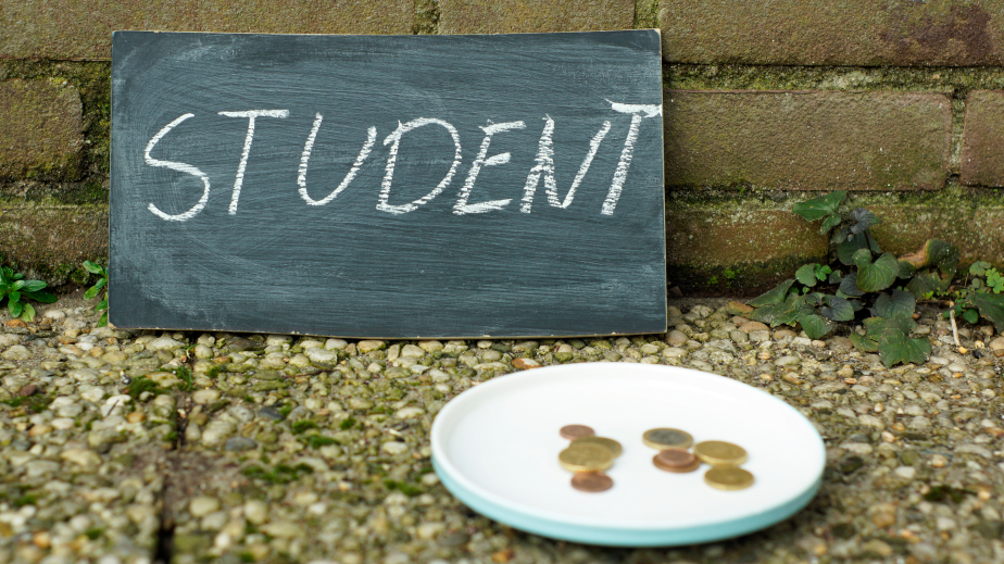 sign that says student next to a dish for spare change
