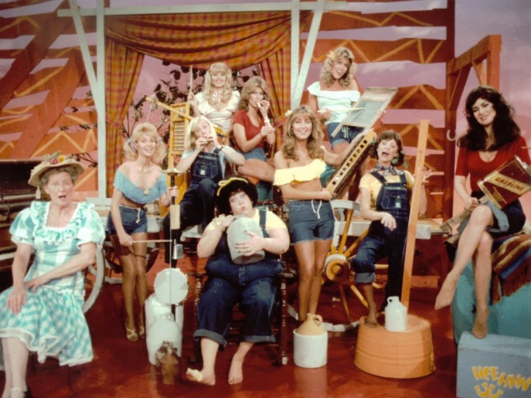 A group of women play instruments in overalls in Hee Haw Honeys