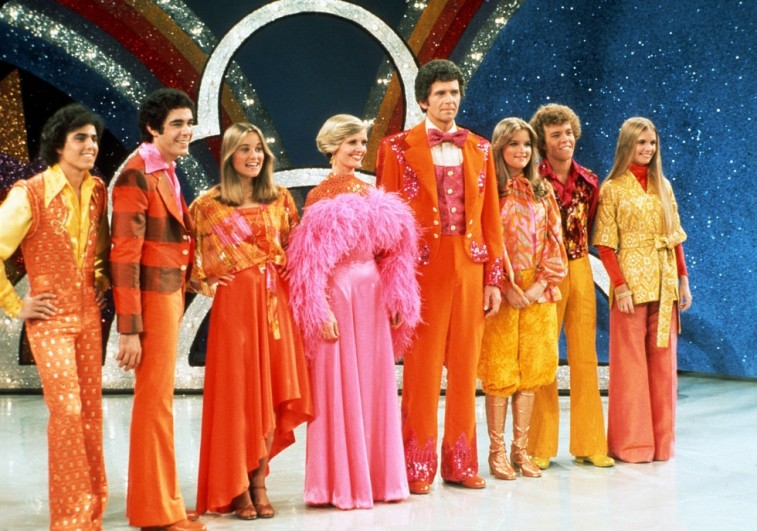 The Brady Bunch cast stand on stage in a line while wearing colorful outfits in The Brady Bunch Hour