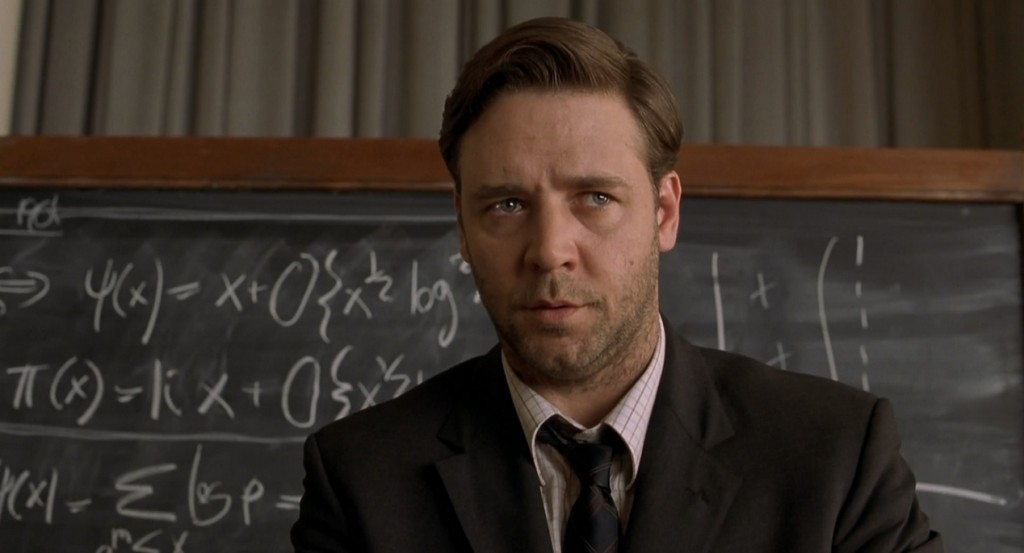 Russell Crowe is in a suit and is standing in front of a chalk board.