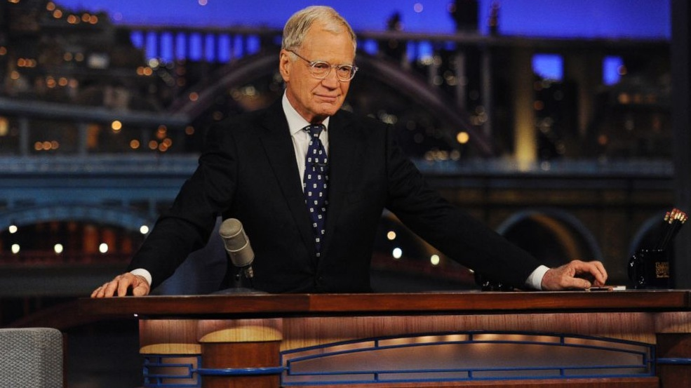 David Letterman is sitting at his desk on The Late Show.
