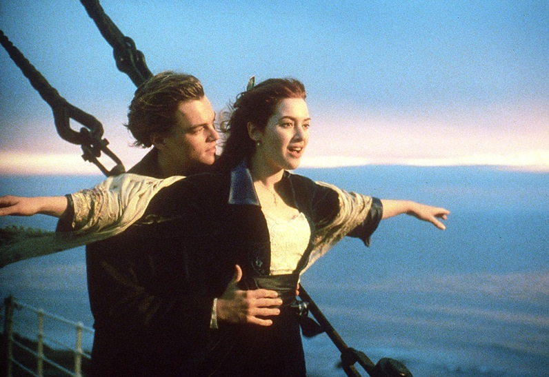 Leonardo DiCaprio embracing Kate Winslet with her arms out, smiling