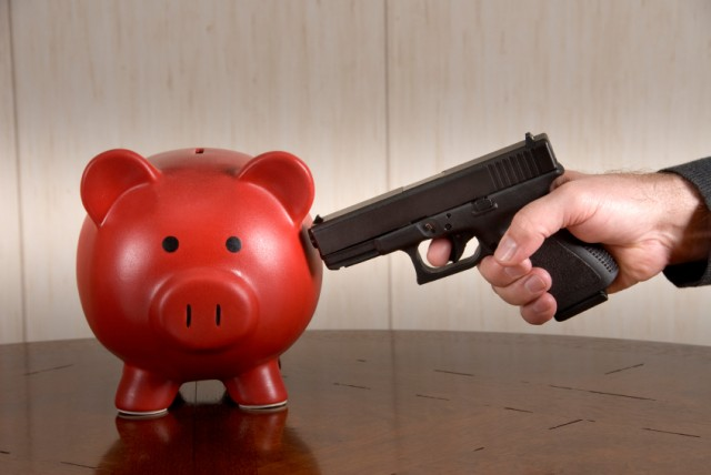 gun pointed at piggybank