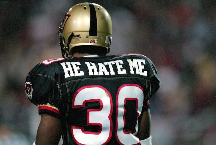 """A football player shows the back of his jersey which reads """"He Hate Me' above the number 30 in X.F.L."""