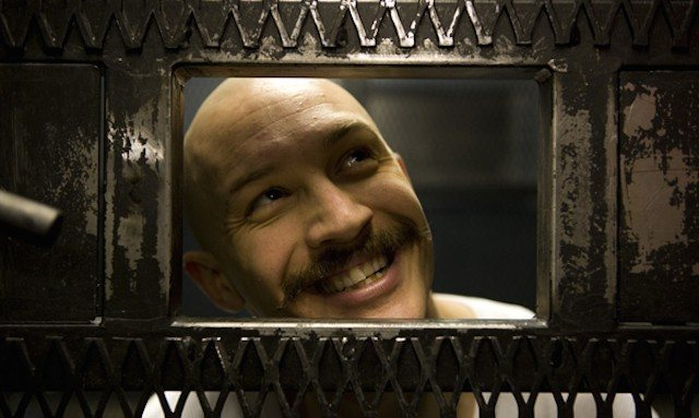 Tom Hardy smiles while looking out the window of a jail cell in Bronson