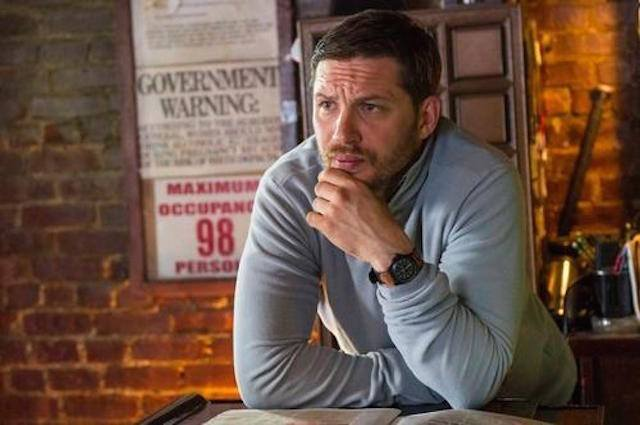 Tom Hardy rests his chin in his hands on a counter