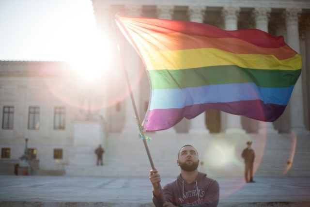 man waving gay pride flag in front of courthouse