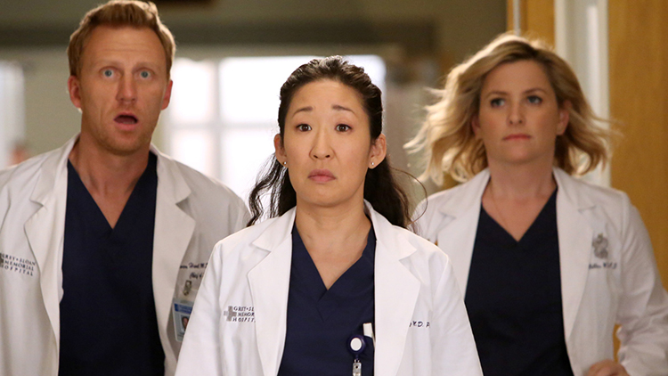 Three doctors from Grey's Anatomy look on in shock as they walk down a hallway