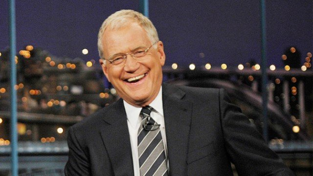 David Letterman sitting in a dark suit during his show.