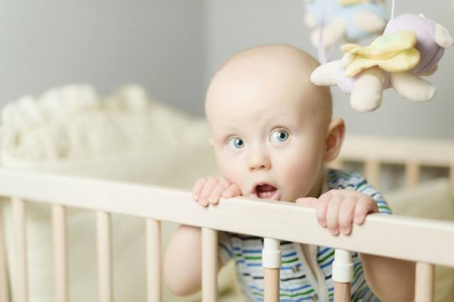 little baby standing in a crib